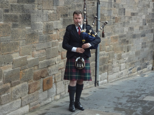 A bagpiper pipes a lively tune outside Edinburgh Castle in Scotland.